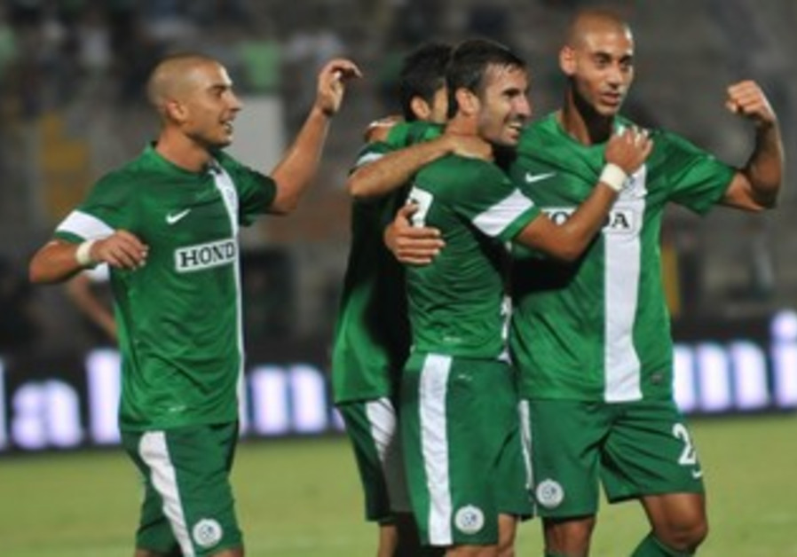 MACCABI HAIFA'S players (left) had plenty of reasons to embrace.