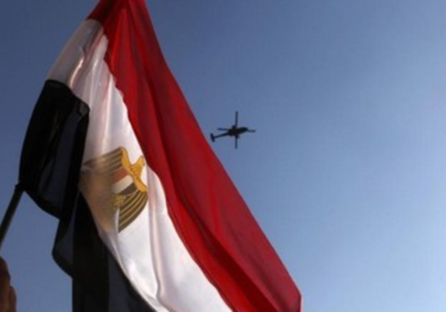An anti-Morsi protester waves an Egyptian flag as a military helicopter passes over Tahrir square.