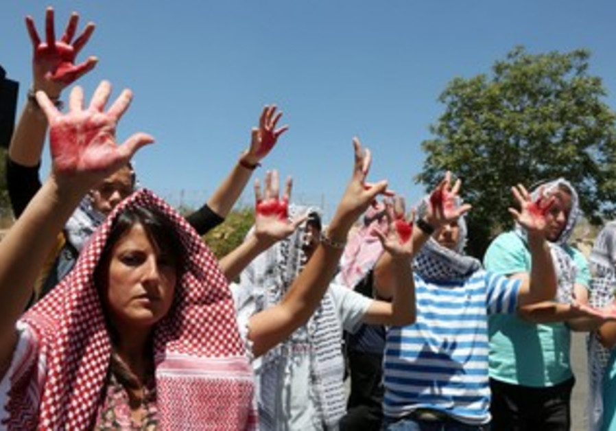 Israelis wearing keffiyehs with hands covered in fake blood protest the release of prisoners.