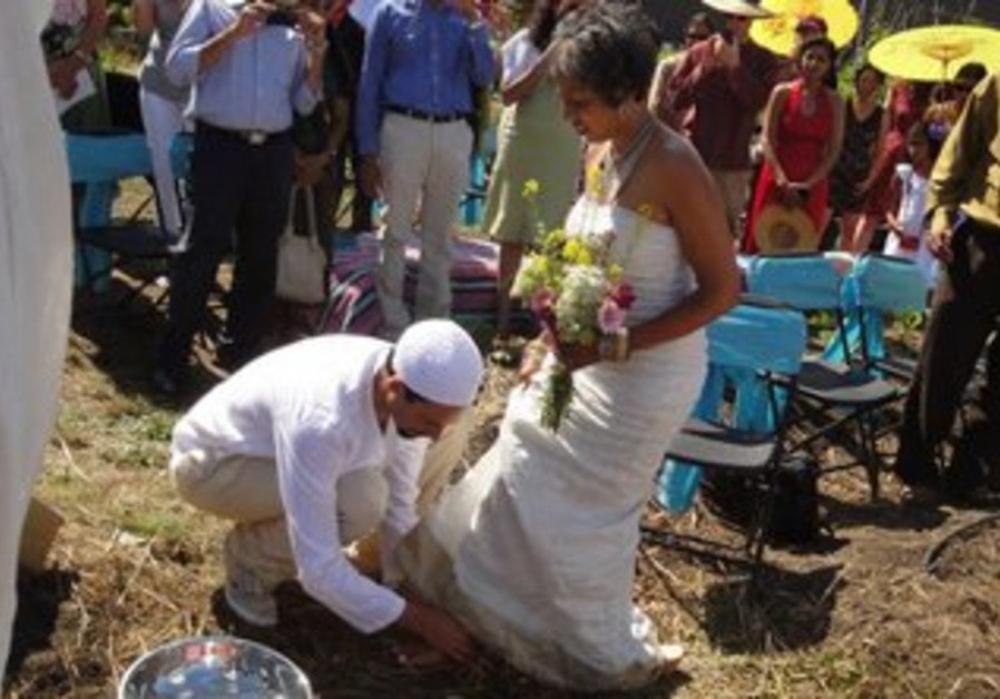 The groom washes the feet of his bride during the wedding