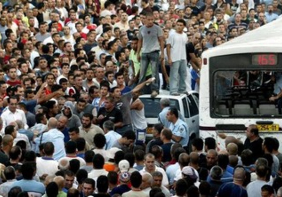 A crowd of Israeli Arabs surrounds a bus following a shooting attack in the town of Shfaram August 4