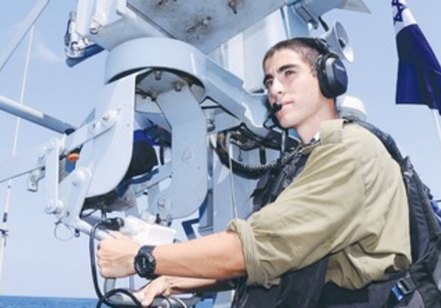 SGT. NITAY EFERGAN of the Israel Navy stands aboard his ship near the Gaza border.
