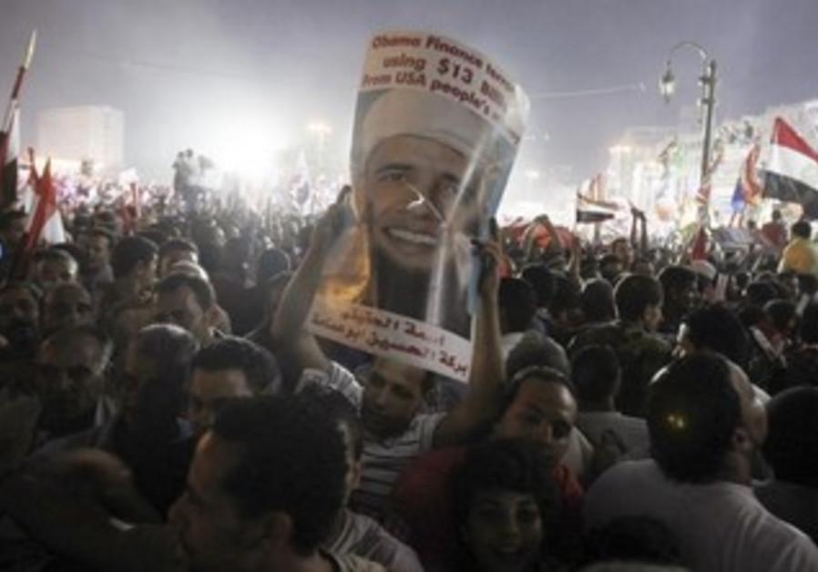 Anti-Morsi protesters hold up anti-Obama sign in Tahrir square, July 29, 2013.