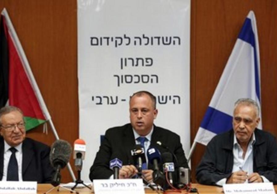 Israeli member of parliament Hilik Bar (C) sits next to Abdullah Abdullah (L).