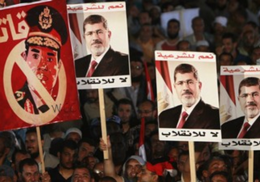 "Morsi supporters hold up posters, including of Egypt army chief Sisi that reads, ""murderer"""