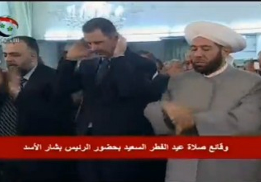 Assad attends Eid al-Fitr prayers in Damascus following reports his convoy was targeted.