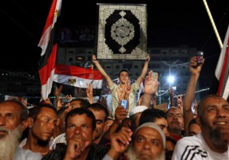 A supporter of deposed Egyptian President Mohamed Morsi holds up a Koran during a protest.