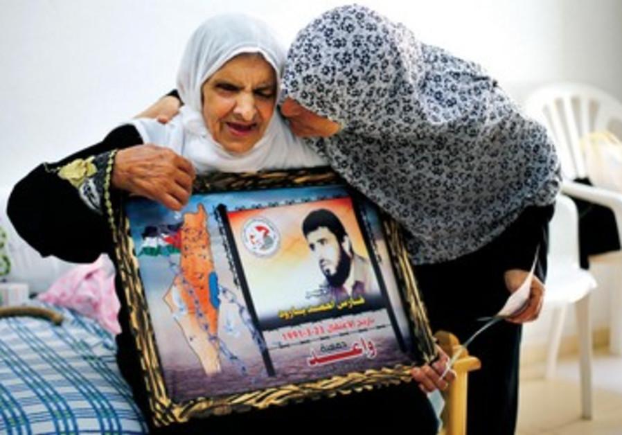 Une habitante du camp de Gaza tenant une affiche de son fils purgeant une peine de prison de 22 ans.
