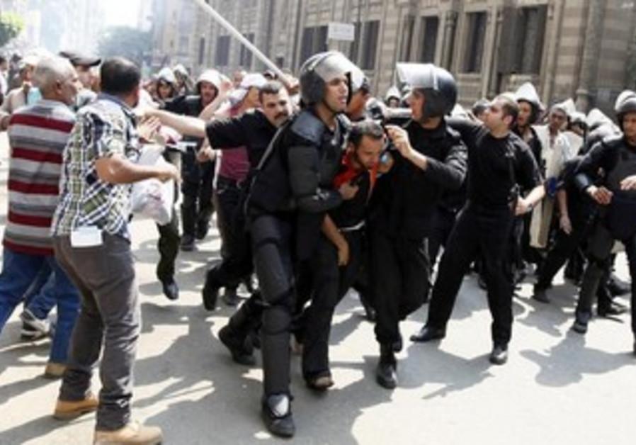 Police detain a supporter of ousted Egyptian President Mohamed Morsi in Cairo August 13, 2013.