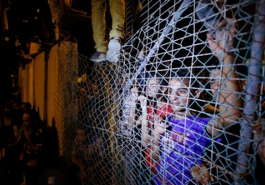 Gazans wait near the Erez crossing for Palestinian prisoners freed by Israel, August 13, 2013.
