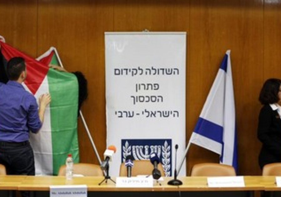 Israeli parliament employees set up a Palestinian flag (L) next to an Israeli ahead of peace talks