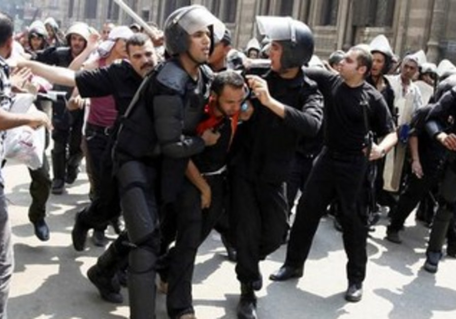 Police detain a supporter of Morsi during clashes in central Cairo August 13, 2013.
