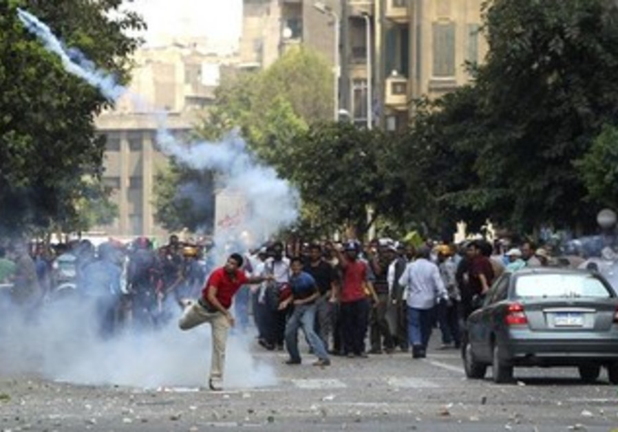 Pro-Morsi supporter throws a tear gas canister back towards the police during clashes in Cairo.