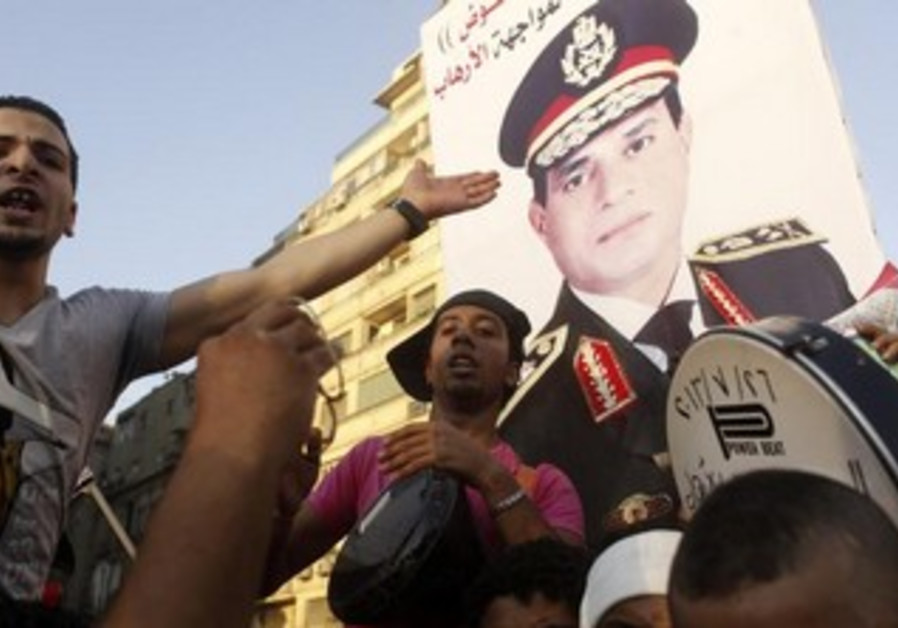 Protesters cheer with drums near a poster of army chief Abdel-Fattah El-Sisi in Cairo