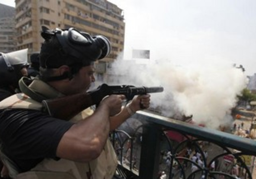Riot police fire tear gas during clashes with Morsi supporters in Cairo, August 14