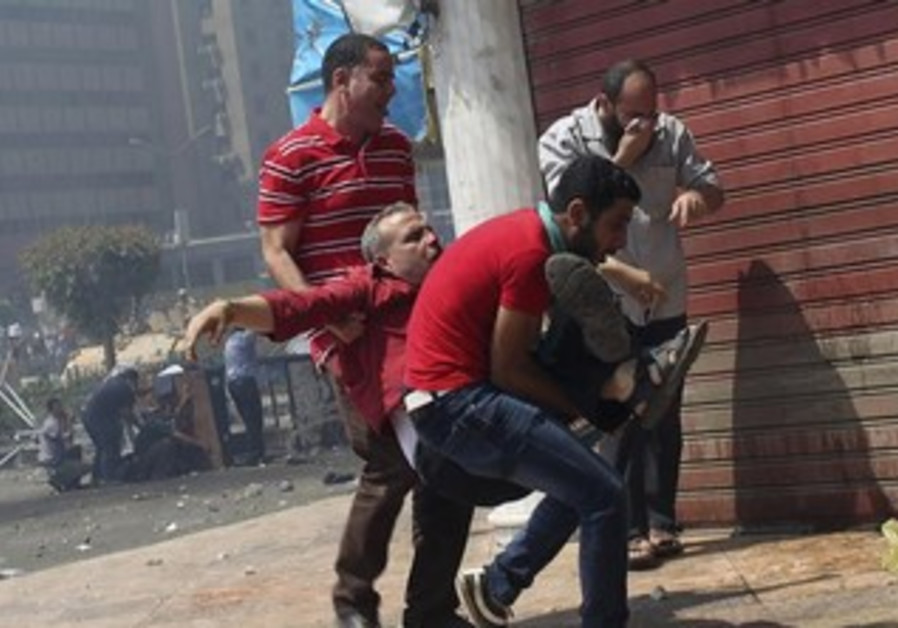 Protesters carry injured man in Cairo, August 14