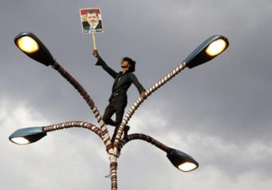 A Morse supporter waves his banner from atop a street light.