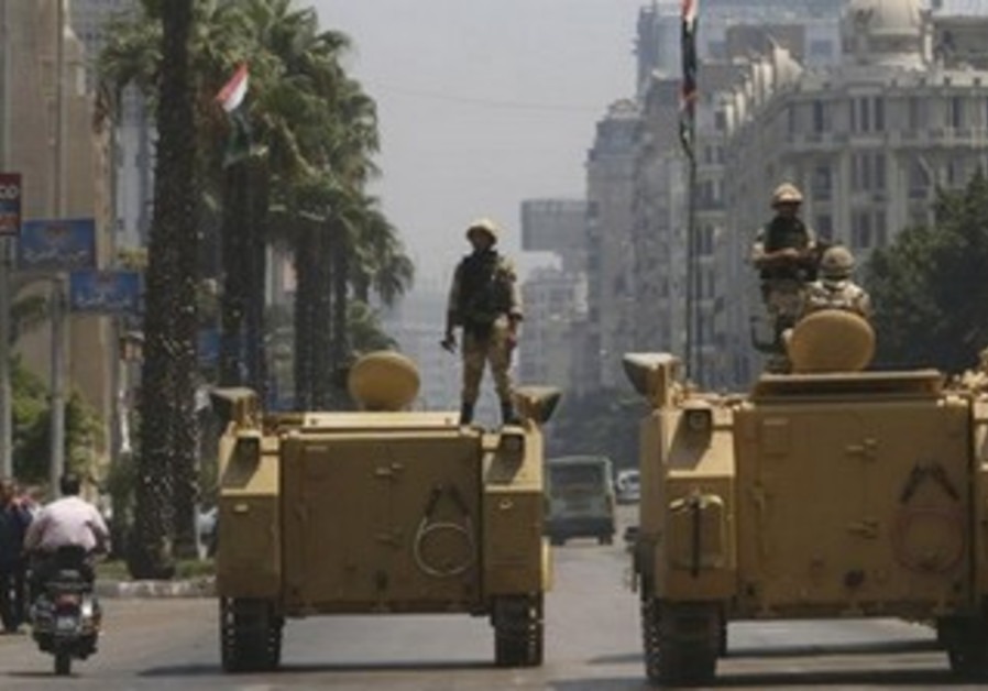 A soldier holds his weapon as he stands on an APC in Cairo, August 16, 2013.