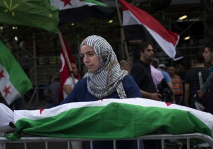 Protester holds mock corpse covered in Syrian flag in front of UN in New York, August 21