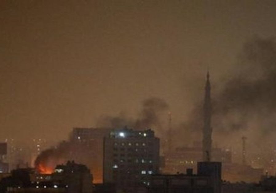 Smoke rises over Cairo at night.
