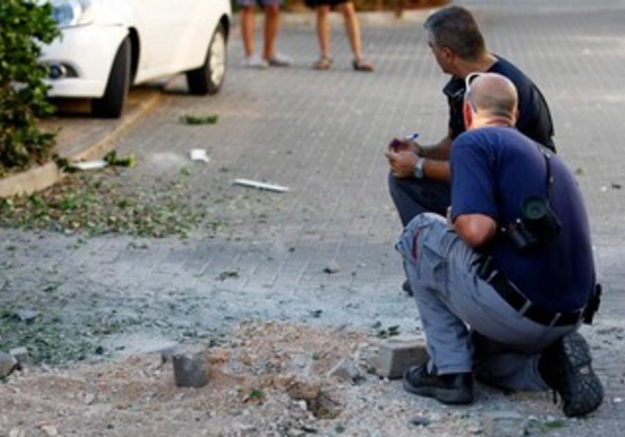 Israeli police survey damage to a village near Nahariya following Thursday's rocket attack.