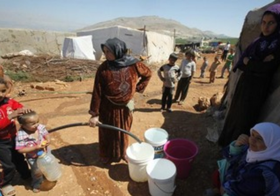 Syrian refugees fill buckets with water.