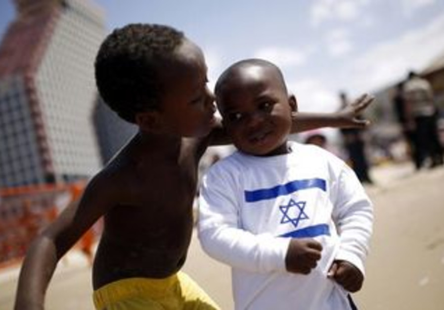 Children of migrant workers play on a beach in Tel Aviv,