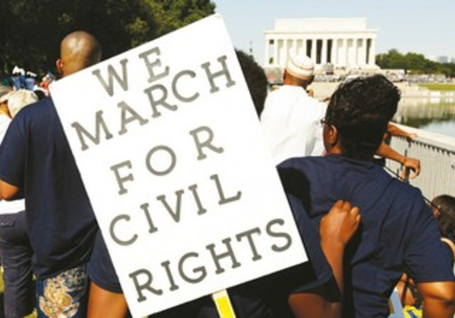 AN AMERICAN holds a sign commemorating the US civil rights march on Washington in 1963.