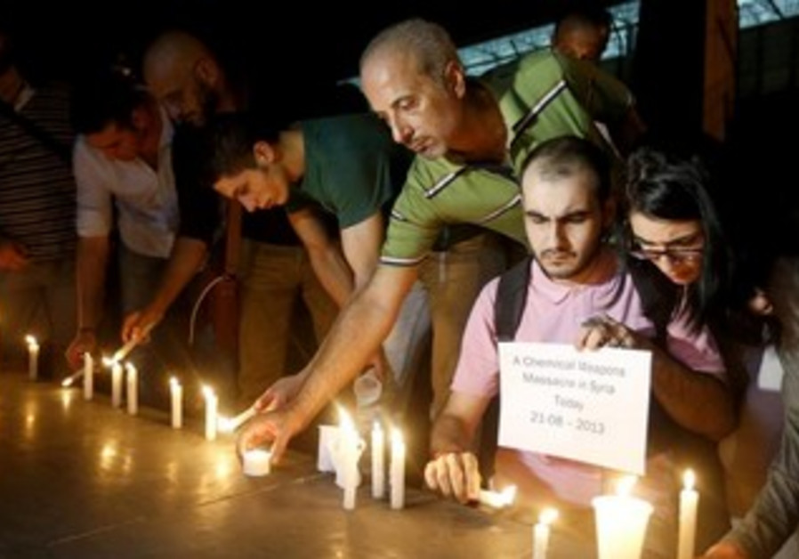 Syrian civilians take part in a candlelight vigil in solidarity with Syrian civilians killed.