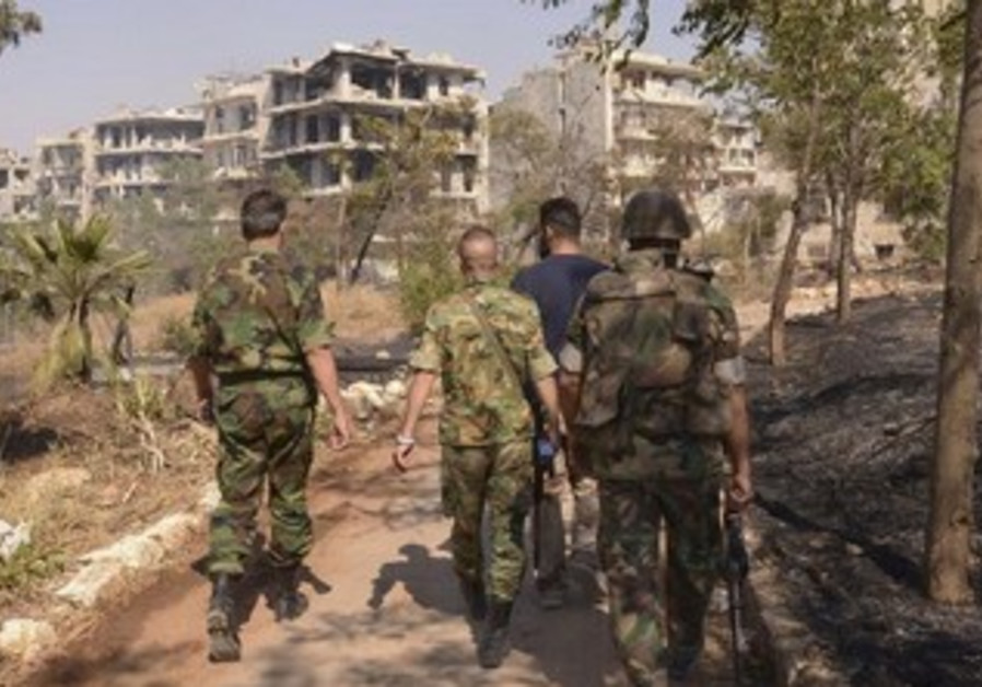 Forces loyal to Syria's President Bashar Assad walk towards the front line.