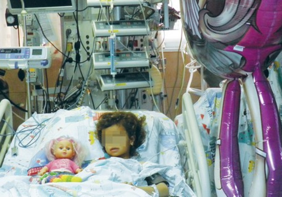 AN INJURED eight-year-old girl lies in bed after her home was hit by a rocket.