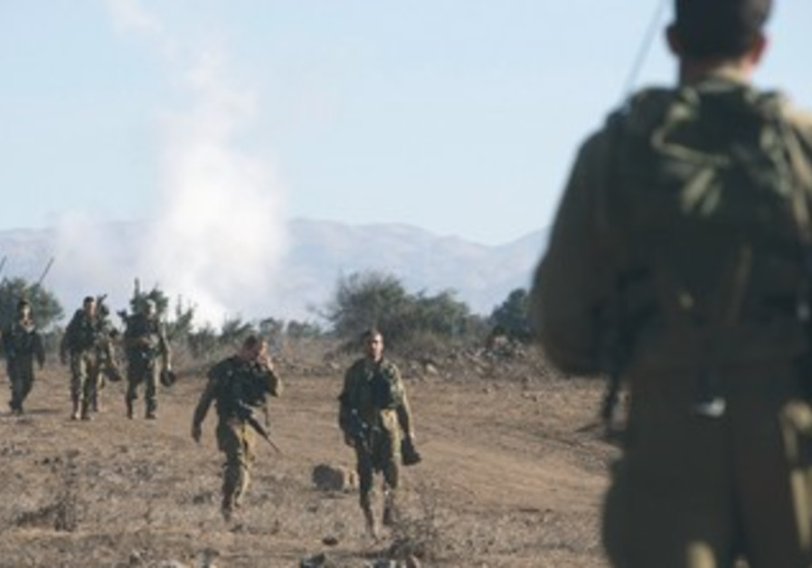 IDF SOLDIERS take part in a drill on the Golan Heights, near the Syrian border, yesterday.