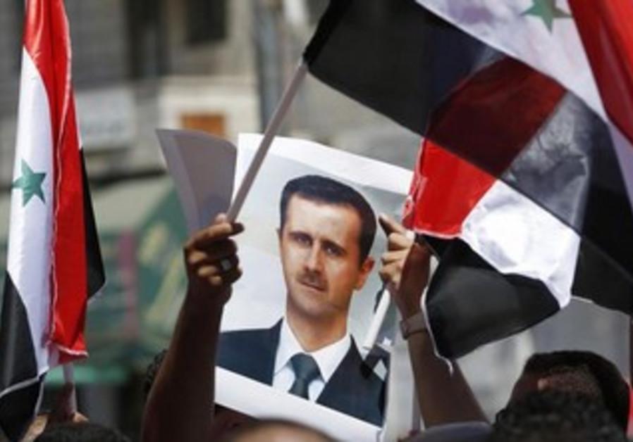 Protester holds a poster of Syria's President Bashar Assad