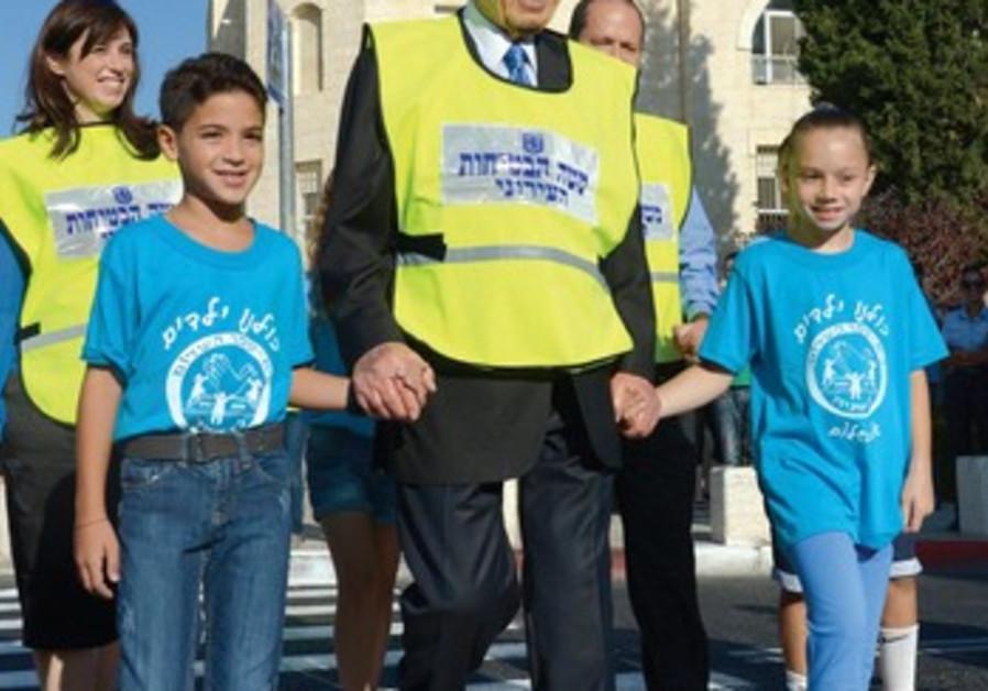 Le président Shimon Peres, main dans la main avec les élèves pour le premier jour d`école.