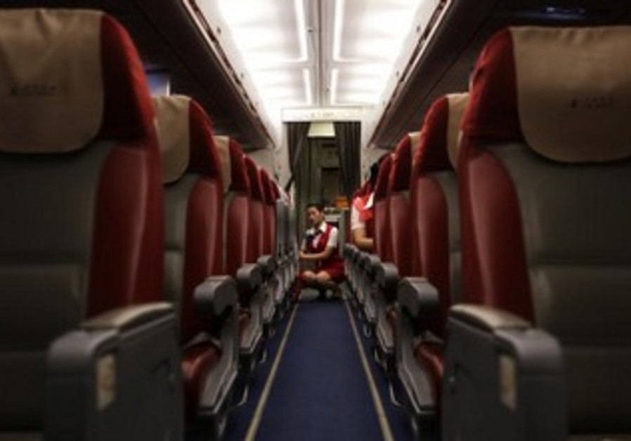 A female flight attendant readies plane before boarding.