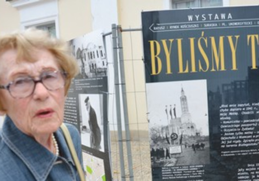 EWA KRACOWSKA stands in front of a poster for an exhibit on Jewish life in Bialystok.