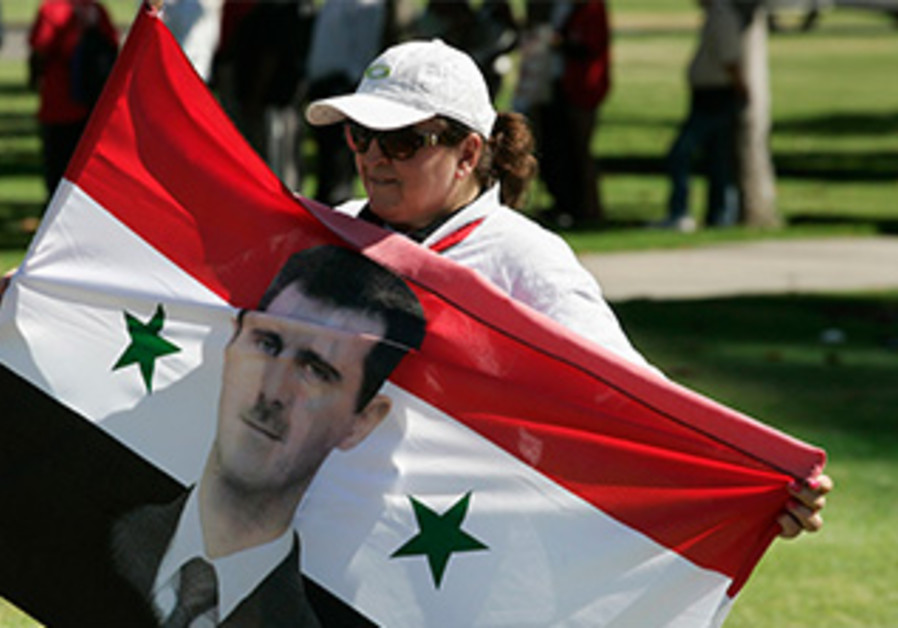 A protester holds a Syrian flag with an image of Bashar Assad at a rally in L.A., Sept. 7,  2013.