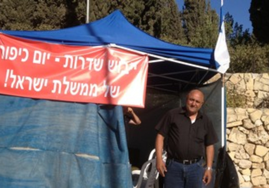 Sderot Mayor David Bouskila stands in front of his protest tent .