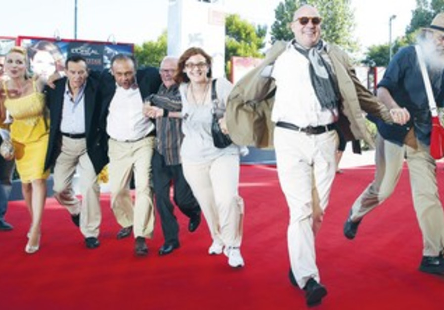 DIRECTOR GIANFRANCO Rosi poses with his cast for the movie 'Sacro GRA' at 70th Venice Film Festival