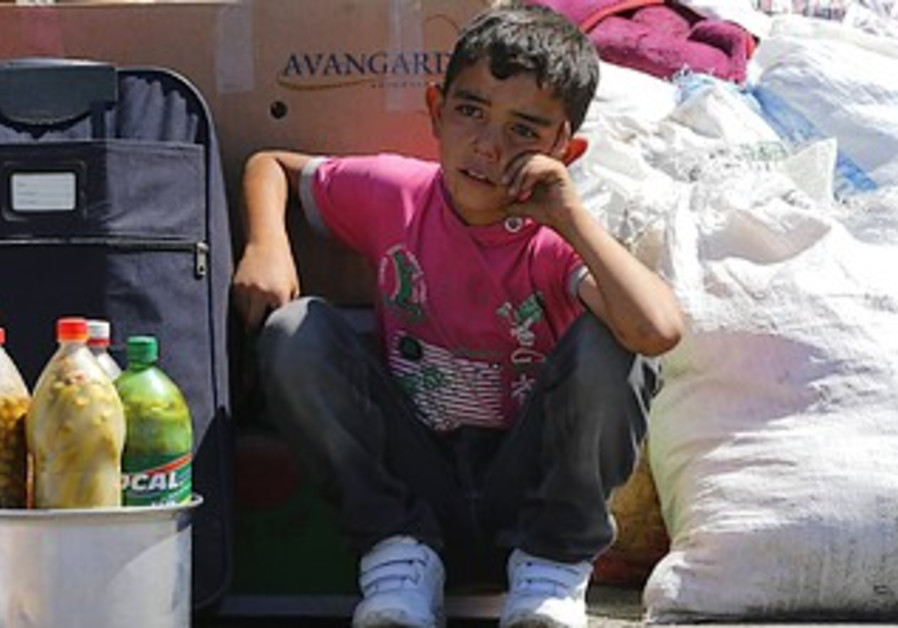 A Syrian boy sits beside his family's belongings after entering Turkey from Syria, Sept. 6, 2013.