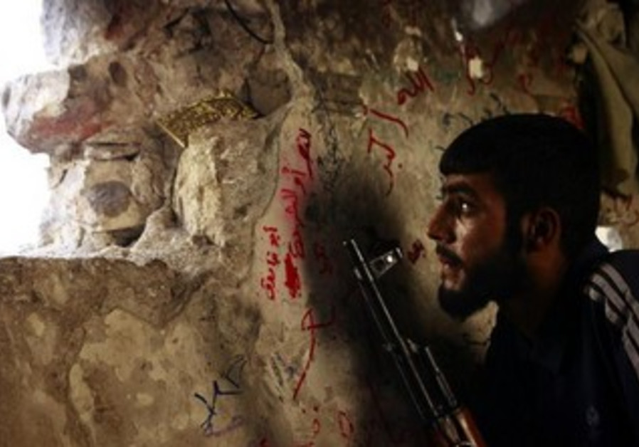 A Free Syrian Army fighter sits on a lookout for forces loyal to Assad September 8, 2013.