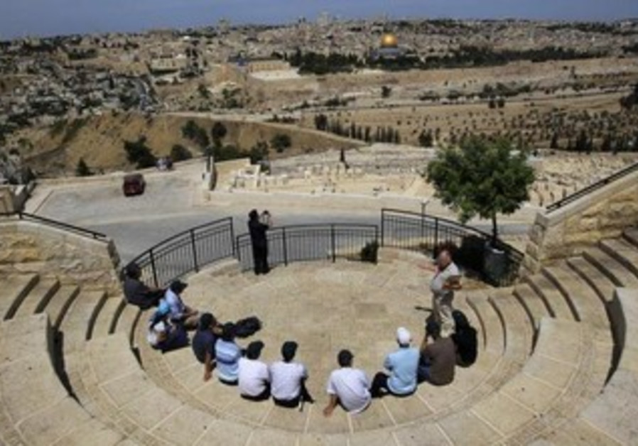 Tourists sit at a lookout point on the Mount of Olives, overlooking Jerusalem's Old City.