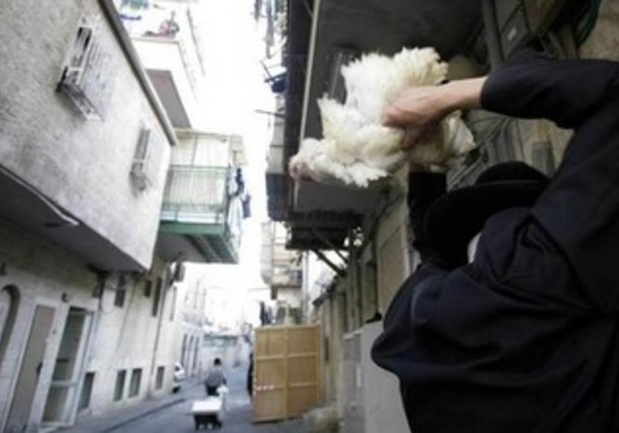 A Haredi Jew swings a chicken over his head during Kapparot in the Mea Shearim area of Jerusalem.