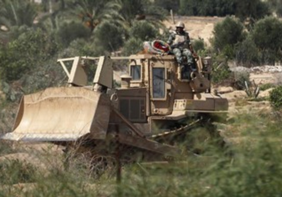 Egyptian soldier sits on a bulldozer near Rafah