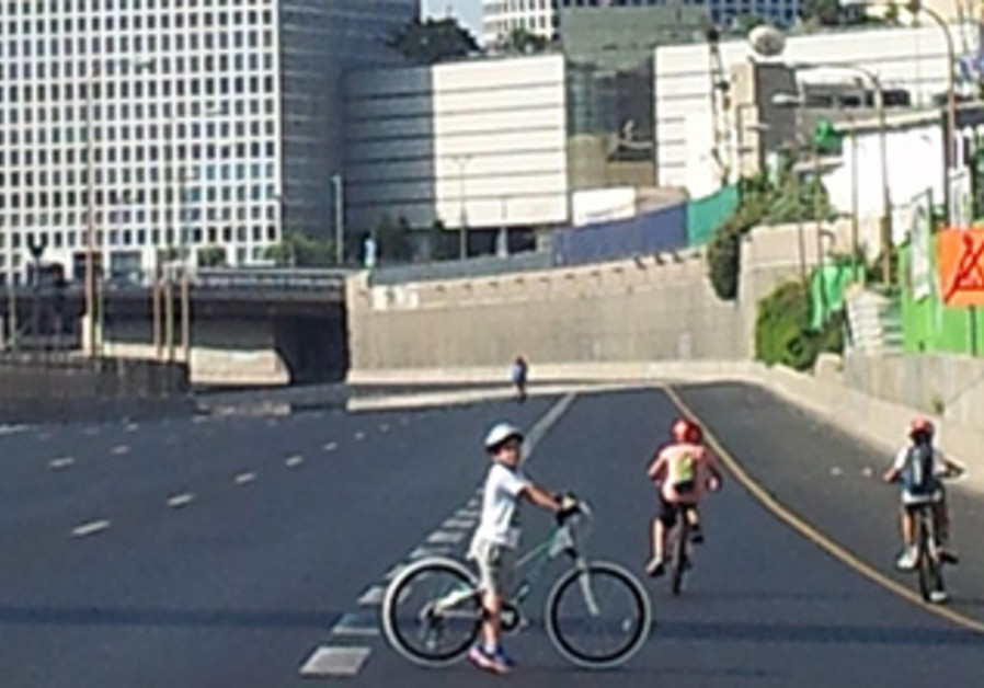 Amit Steinbach, 10, and friends cycle down a deserted Ayalon Highway in Tel Aviv on Yom Kippur.