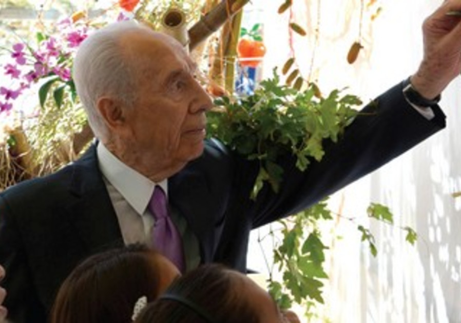 Shimon Peres decorating the Presidential Succa