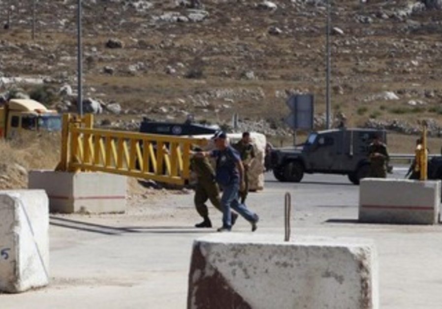 Soldiers and a security personnel open the gate of a check-point in the West Bank city of Hebron.