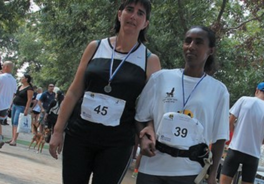 THE BLIND run side by side with accompanying sighted runners.