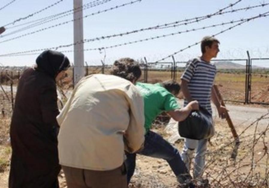 Syrian refugees cross border into Turkey near Azaz, Syria.