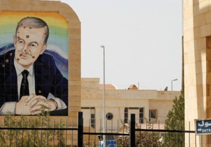 A BULLET-riddled portrait of late Syrian leader Hafez al-Assad.